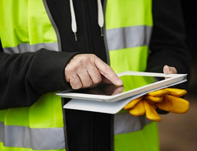 construction worker holding tablet GovPilot government software